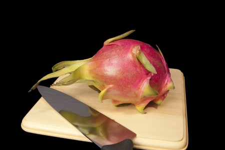 This is a dragon fruit over a cutting board on a black background.