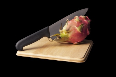 A dragon fruit over a cutting board on a black background.