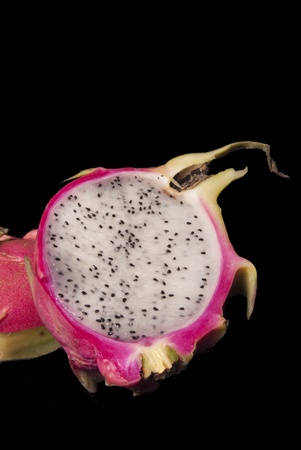This is a half of a dragon fruit on a black background.