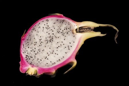 A half of a dragon fruit on a black background.