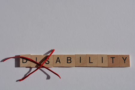 Creative Concept : Disability in wooden letters, with Dis crossed out, leaving the word Ability