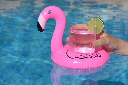 Hand holding a drink in an inflatable pink flamingo drinks holder in swimming pool