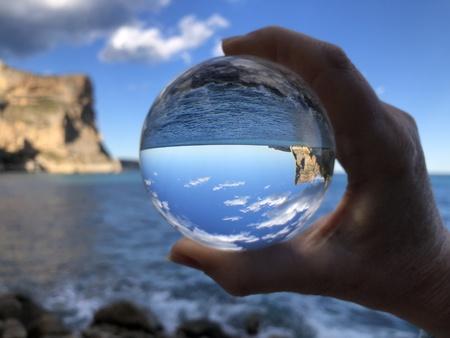 Mano sosteniendo una bola de cristal, mirando hacia el horizonte, el mar y el cielo. Fotografía creativa, refracción de bola de cristal. Foto de archivo