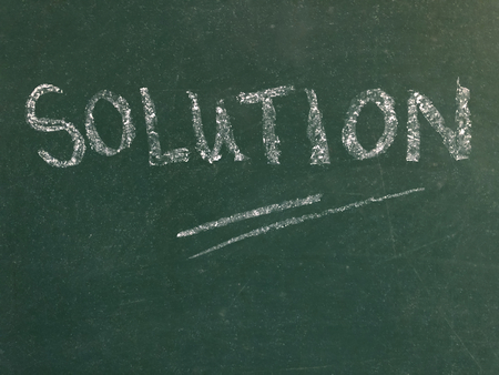 The word Solution written in white chalk on a chalk board, with copy space