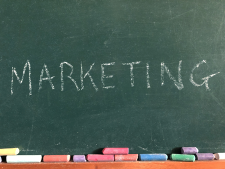 The word Marketing written on a chalk board with coloured chalk sticks beneath 版權商用圖片