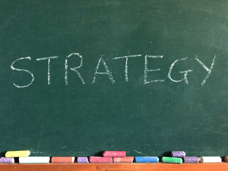 The word Strategy written on a chalk board with coloured chalk sticks beneath 版權商用圖片