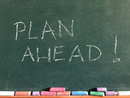 The words Plan Ahead ! written on a chalk board with coloured chalk sticks beneath