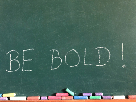 The words Be Bold! written on a chalk board with coloured chalk sticks beneath 版權商用圖片