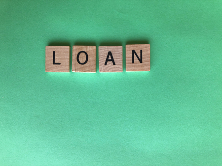 Banking  and Finance, creative concept. Wooden letters spelling the word Loan on a plain green background with copy space
