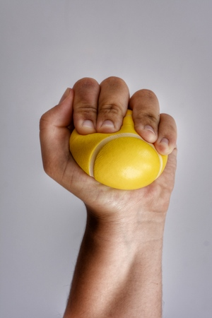 Stressed out woman squeezing a yellow stress ball in her clenched fist Banque d'images