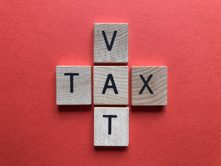 VAT (acronym for Value Added Tax) and Tax in 3d wooden alphabet letters on a bright red background Archivio Fotografico
