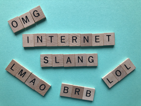 Internet slang. Acronyms : BRB (Be Right Back), LOL, OMG, and LMAO used as abbreviations in text messages, in wooden letters on a turquoise background with copy space.