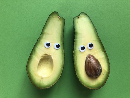Creative fun healthy food photography. Avocado cut in half with googly eyes, one half with the seed, the other without. Stock Photo