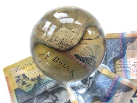 Australische 50-Dollar-Banknote und eine 1-Dollar-Münze durch eine Kristallkugel gesehen. Vorhersage des Terminmarktes. Kreatives Konzept, Bank- und Finanzwesen. Australien