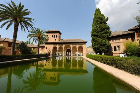 Pond reflections and visitors at the open portico of Torre de las Damas, Tower of The Ladies, Partal, The Alhambra, Granada, Andalusia, Spain