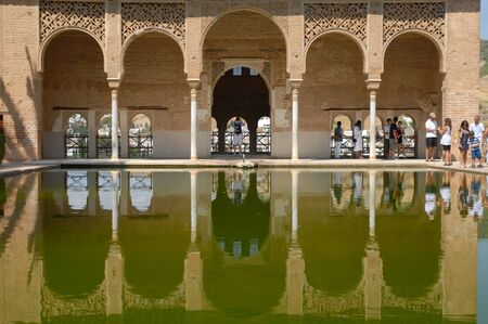 Reflections in pond water and visitors at the open portico of Torre de las Damas, Tower of The Ladies, Partal, The Alhambra, Granada, Andalusia, Spain Editorial