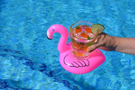 Woman holding glass decorated with pineapples, of sparkling water with a slice of lime, in a pink inflatable flamingo drinks holder in a swimming pool.