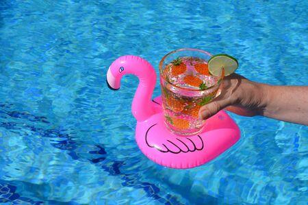 一个女人在游泳池里拿着装饰有菠萝的玻璃杯,里面装着苏打水和一片酸橙。
