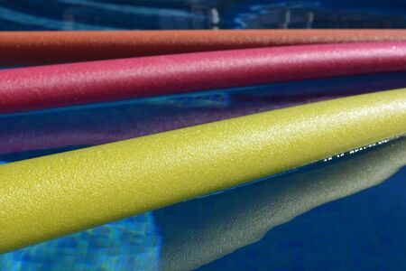 Bright yellow, pink and orange pool noodles, floating in a swimming poo Banco de Imagens