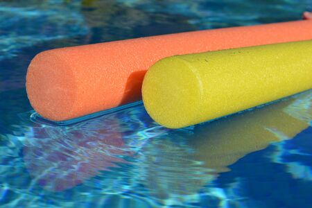 Bright yellow and orange pool noodles floating in a swimming pool