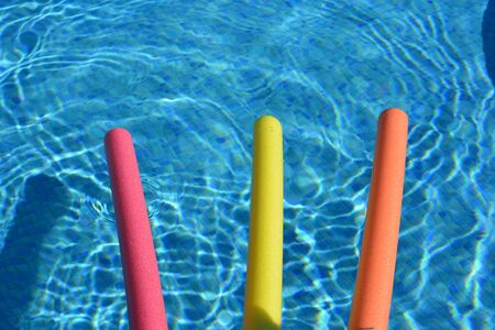 Bright yellow, pink and orange pool noodles, floating in a swimming pool. Top view