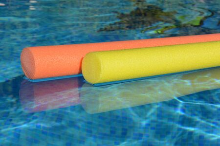 Bright yellow, pink and orange pool noodles, floating in a swimming pool