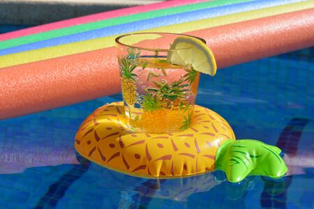 Vaso de agua en un soporte inflable de piña y fideos de piscina flotando en una piscina. Vibraciones de verano, brillantes y coloridas, manteniéndose frescas