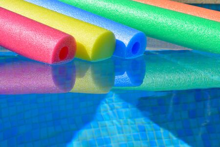 pool noodles floating in a swimming pool. Summer vibes, bright and colourful, keeping cool
