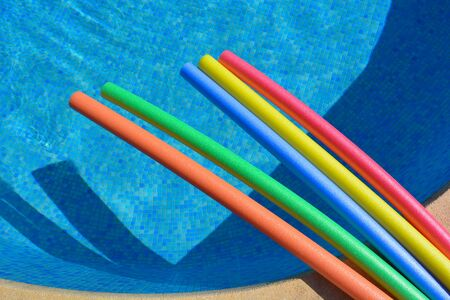 Swimming pool with brightly coloured pool noodles on the poolside, from above with copy space. Fun summer vibes. Banco de Imagens