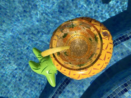 Glass of sparkling water and slice of lemon in an inflatable pineapple drink holder floating in a swimming pool, top view with copy space