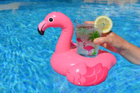 Woman holding a pink flamingo inflatable drink holder with a plastic cup decorated with palms, flamingoes and a slice of lemon. Fun summer fun vibes, keeping cool in the swimming pool Banco de Imagens