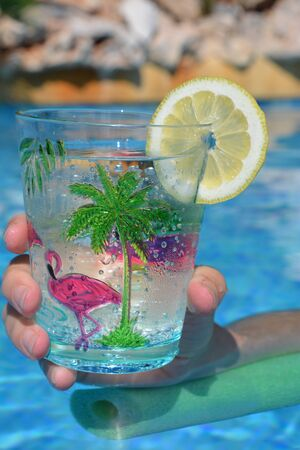 Hand holding glass decorated with pink flamingoes in swimming pool. Fun summer vibes, keeping cool