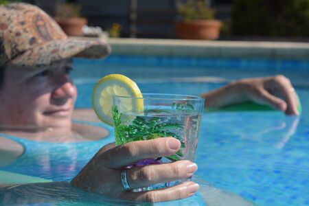 Candid portrait of woman holding a drink in a swimming pool, floating on a pool noodle. Selective focus, hand holding cup.