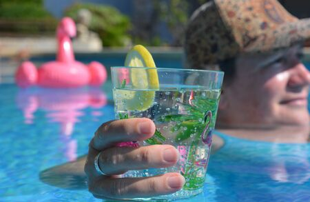 Woman in swimming pool holding a drink, selective focus on hand holding plastic cup