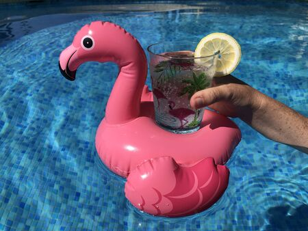 Hand holding a drink in an inflatable pink flamingo drinks holder in swimming  pool.