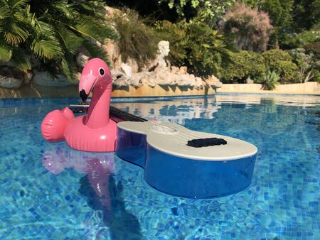 Inflatable pink flaming and a blue plastic ukulele floating in a swimming pool. Summer fun, leisure and recreation
