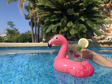 Inflatable pink flamingo drink holder and womans hand in swimming pool