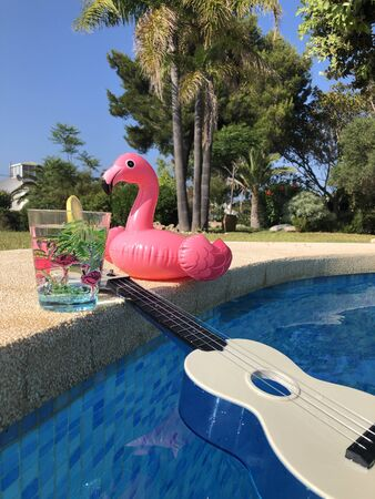 Inflatable pink flaming and a glass of water on the poolside, next to a blue and white ukulele floating in a swimming pool