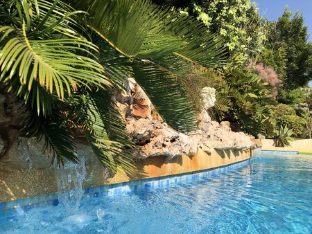 Swimming pool with rockery, water feature and Roman bust in a Mediterranean garden Banco de Imagens