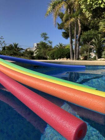 Pool noodles on the poolside of swimming pool in a garden with palm trees