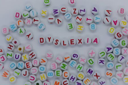 Dyslexia, spelt out in red letters, surrounded by a sea of random letters, on a white background.  Creative concept : reading disability Фото со стока
