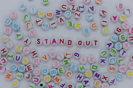 Stand Out, spelt out in red letters, surrounded by a sea of random letters, on a white background.  Creative concept : dare to be different Banco de Imagens