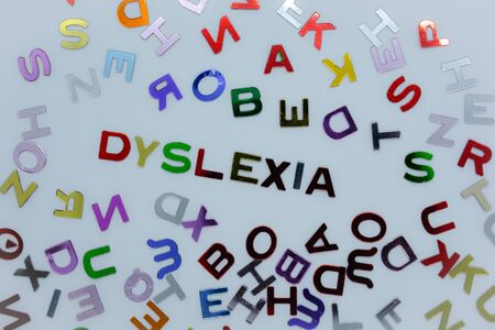 Dyslexia, spelt out in confetti alphabet  letters, surrounded by a sea of random letters, on a white background. Creative concept : reading disability