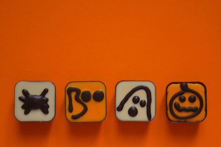 Halloween themed candy chocolates on an orange background with copy space Banco de Imagens