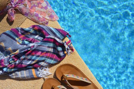 Summer flat lay items, straw hat, beach wrap and sandals on the side of a blue tiled swimming pool with copy space. Banco de Imagens