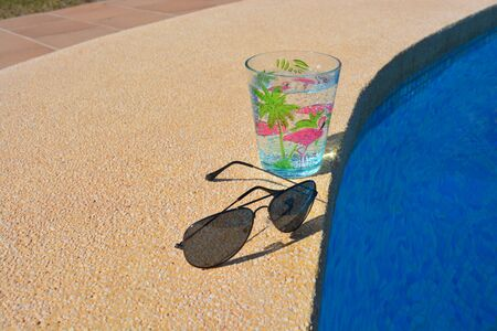 Summer vibes, metal framed dark sunglasses and a drink in a decorated plastic cup, on poolside with copy space Banco de Imagens