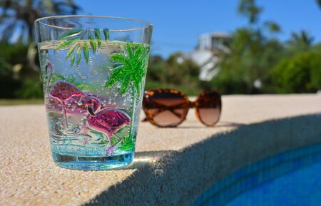 Pool day, summer fun vibes. Sparkling cold water in a tropical themed plastic cup and a pair of plastic tortoiseshell  coloured sunglasses on the poolside.