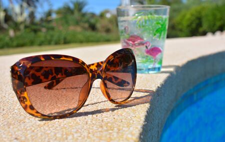 Pool day, summer fun vibes. Pair of plastic tortoiseshell  coloured sunglasses and a sparkling cold drink in a plastic cup on the poolside. 版權商用圖片