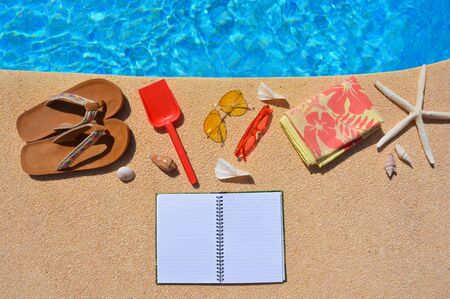 Summer holiday flat lay, Yellow sunglasses, red spade, red shades, starfish, flip-flops. High angle view with copy space Banco de Imagens
