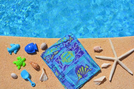Summer holiday flat lay, including starfish seashells and toy beach themed shapes, on the poolside.  Swimming pool high angle view, with copy space. Banco de Imagens